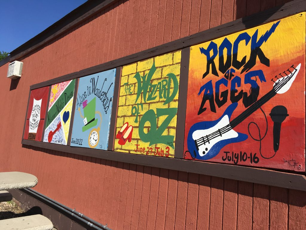 Hand-painted signs outside of the amphitheater. Colorful art for colorful shows!